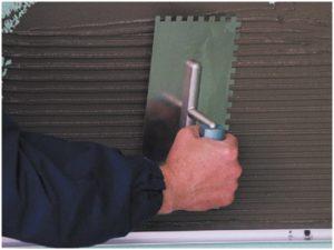 Шпатель для нанесения клеевого состава при проведении работ по отделки стен фасадной штукатуркой