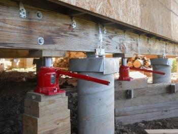 Подъем деревянного дома на домкратах